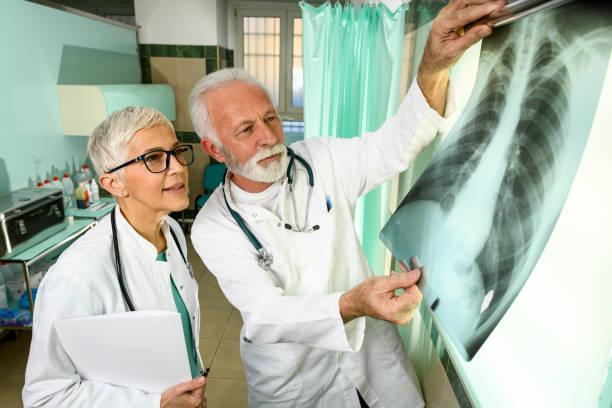 Zwei leitende Ärzte analysieren ein Röntgenbild eines mit Coronavirus infizierten Patienten – Foto
