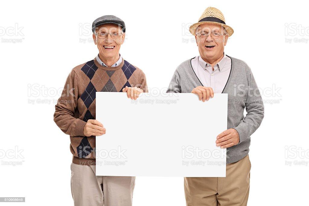 Two senior gentlemen holding a signboard stock photo
