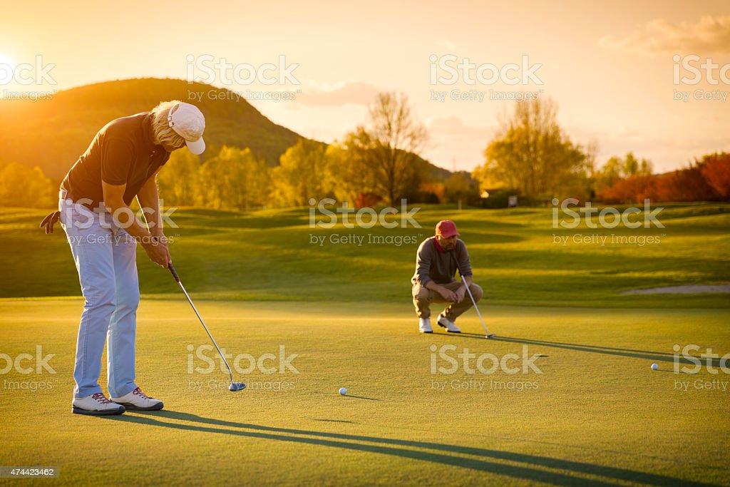 senior deux joueurs de golf au coucher du soleil. - Photo