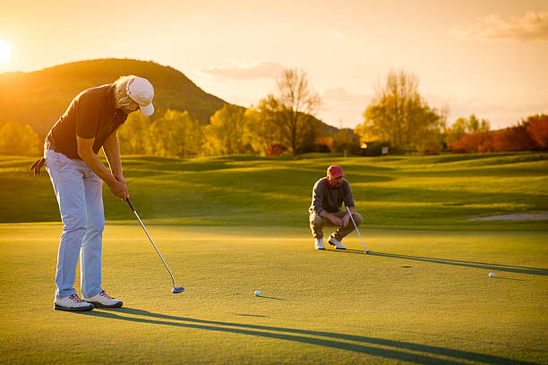 Two senior golf player at sunset. stock photo