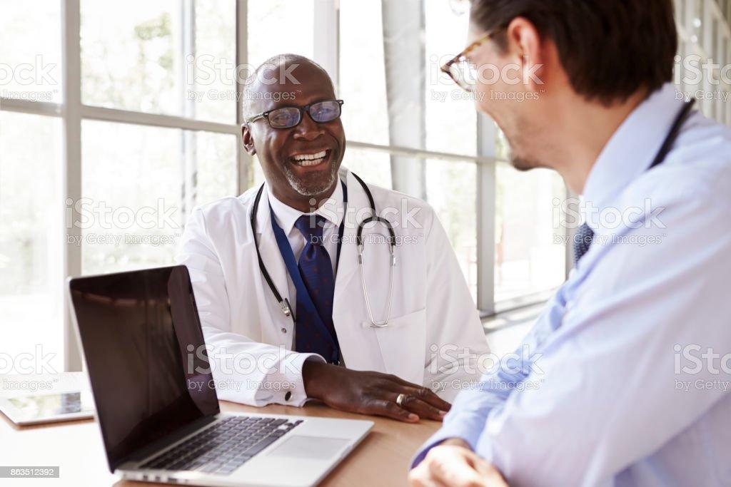 Zwei leitende Pflegepersonal in Absprache lachen – Foto