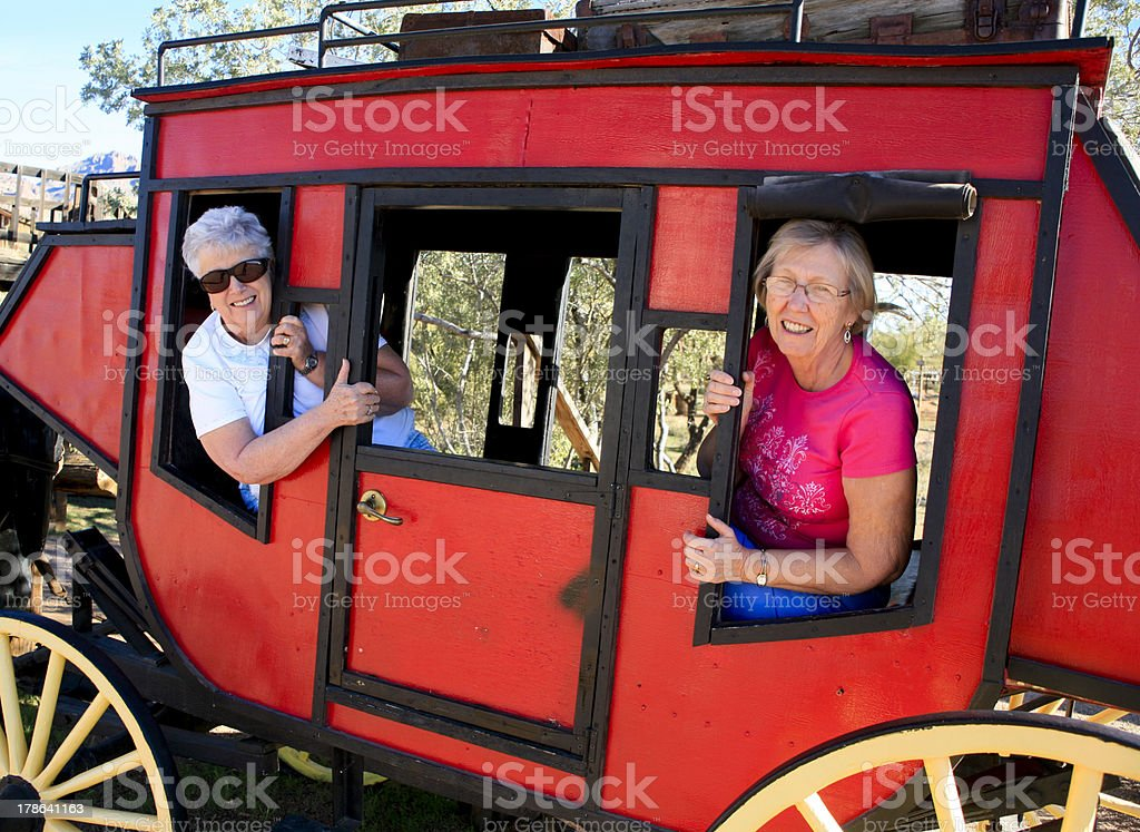 Two Senior Ladies in Red Stage Coach stock photo