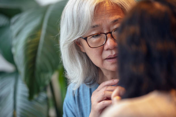 Two senior ladies talking Two Taiwanese senior ladies having a conversation in a café in Taipei. argument of old asian woman and woman stock pictures, royalty-free photos & images