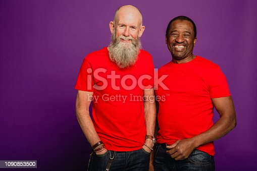 Portrait of a bearded senior man and an African senior man standing in front of a purple background. They are wearing matching red t-shirts.