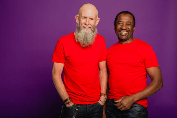 Two Senior Male Friends Laughing Portrait of a bearded senior man and an African senior man standing in front of a purple background. They are wearing matching red t-shirts. red shirt stock pictures, royalty-free photos & images