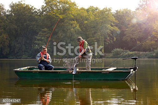 Two senior man catching fish with fishing rod and net on a lake
