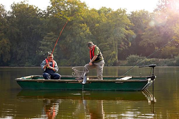 Two senior man catching fish stock photo