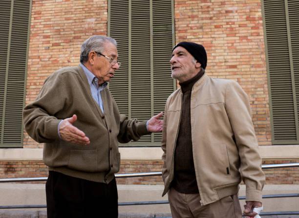 Zwei ältere Männer reden miteinander auf der Straße von Alicante, Spanien. – Foto