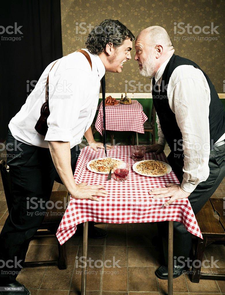 Two Senior Men Arguing Over Italian Pasta Dinner stock photo