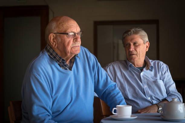 två ledande män tröstar varandra över en kopp kaffe - coffe with death bildbanksfoton och bilder