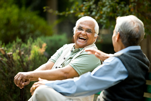 Two retired elderly men sitting on a park bench and having fun