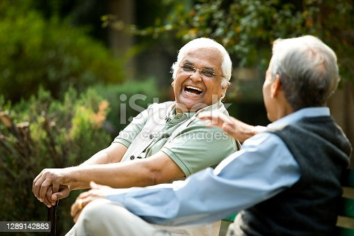 Dos hombres mayores discutiendo en el banco del parque