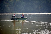 Image of two senior men fishing from a small boat on lake
