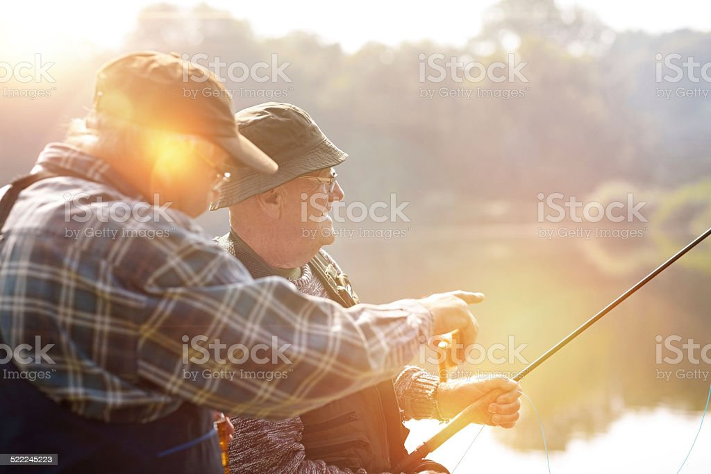 Two senior men fishing on lake stock photo