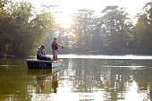 Two senior men in a boat fly fishing on a sunny day