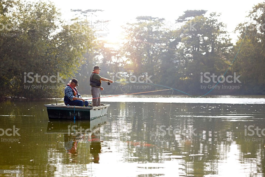 Two senior men in a boat fishing stock photo