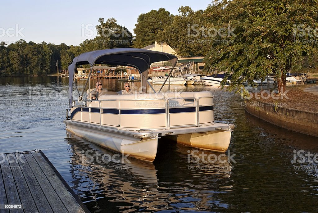 Two senior men riding in a pontoon boat at sunset stock photo