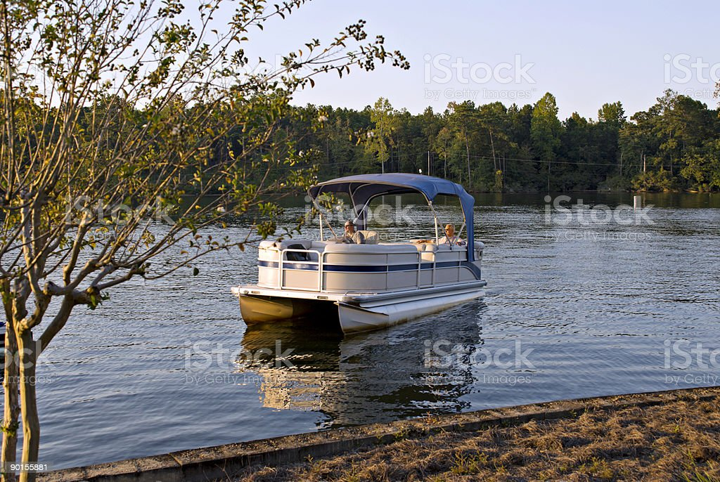 Two senior men riding in a pontoon boat stock photo