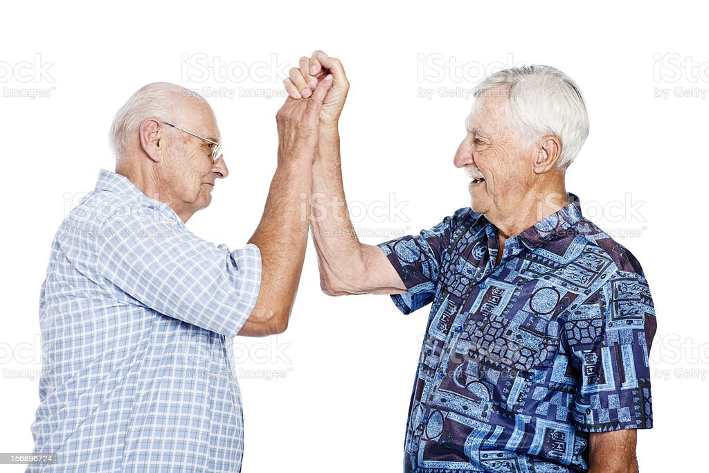 Two senior men smile and exchange a high five stock photo