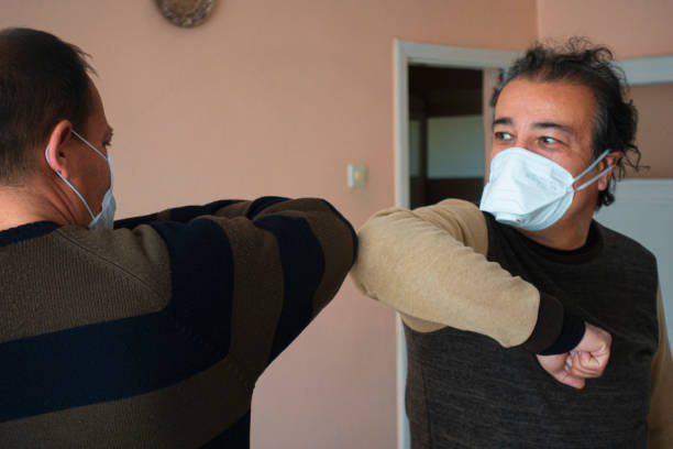Two senior men with masks elbow bumping stock photo