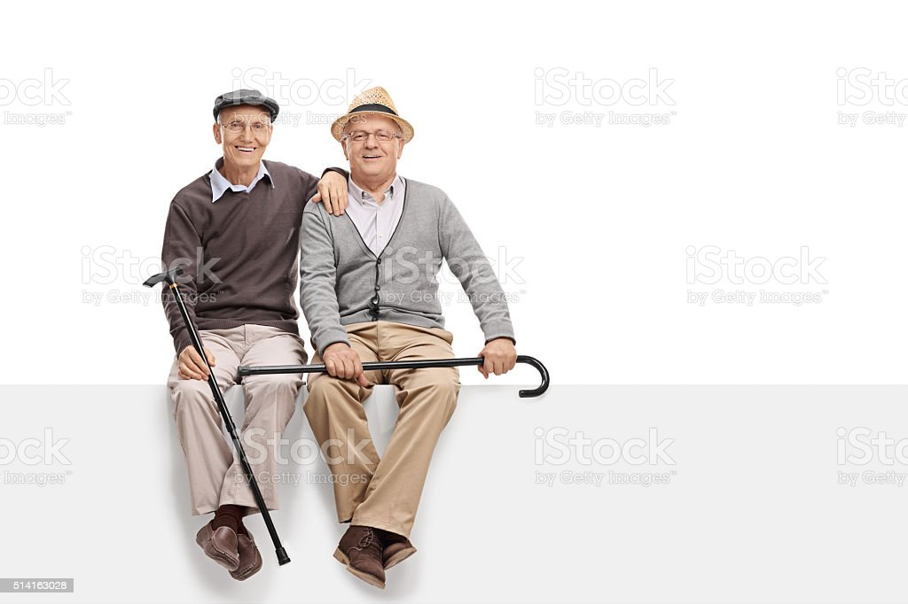 Two senior pals sitting on a blank panel stock photo