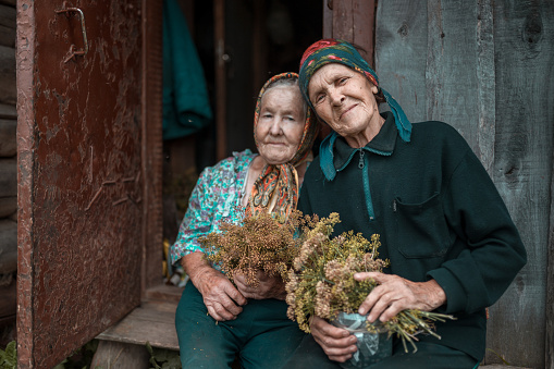 Two senior sisters sits near their obsolete hut at old farm