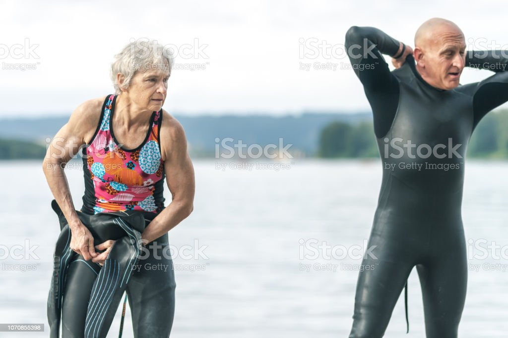 Two senior triathletes - a male and female - change into their...