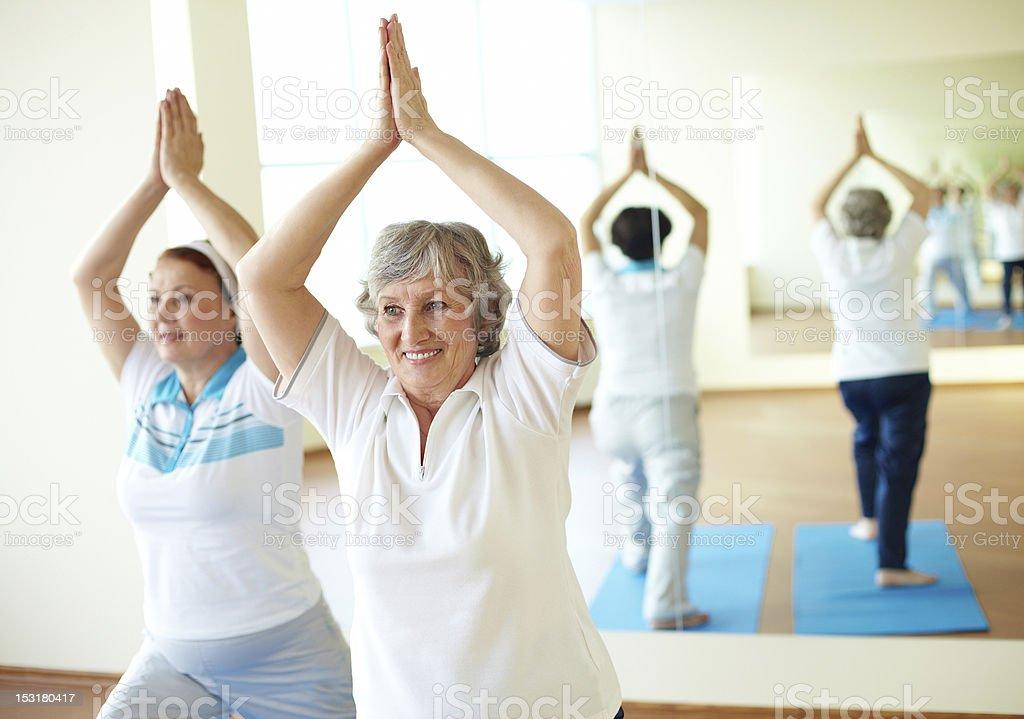 Two senior woman doing a yoga exercise royalty-free stock photo