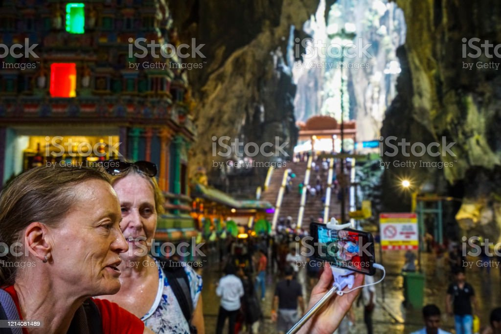 Two senior woman enjoying Batu Caves in Kuala Lumpur, Malaysia Two senior woman enjoying crowed in Batu Cave temple which is one of the most renowned Hinde shrines located outside of India. It is in Kuala Luimpur, Malaysia, Active Seniors Stock Photo