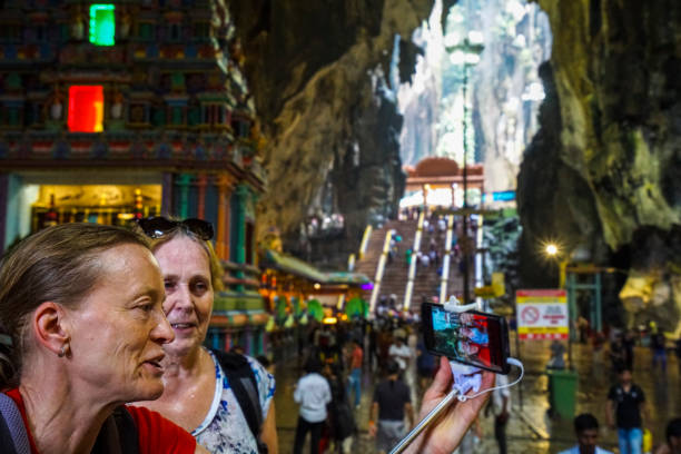 Two senior woman enjoying Batu Caves in Kuala Lumpur, Malaysia Two senior woman enjoying crowed in Batu Cave temple which is one of the most renowned Hinde shrines located outside of India. It is in Kuala Luimpur, Malaysia, batu caves stock pictures, royalty-free photos & images