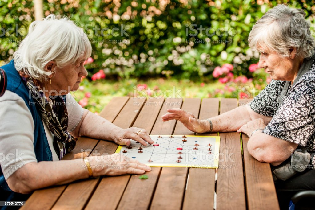 Two Senior Woman In The Retirement Community Playing Muehle Game Board stock photo