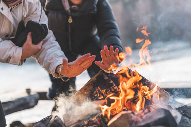 Two senior women by a campfire in winter A couple of active senior women are warming up by a campfire on a beautiful sunny winter day in Sweden. log fire stock pictures, royalty-free photos & images