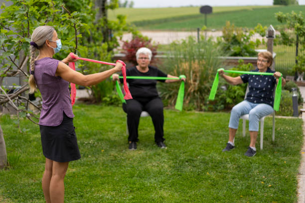 two senior women during healthy fitness training in garden with physical therapist wearing mask stock photo