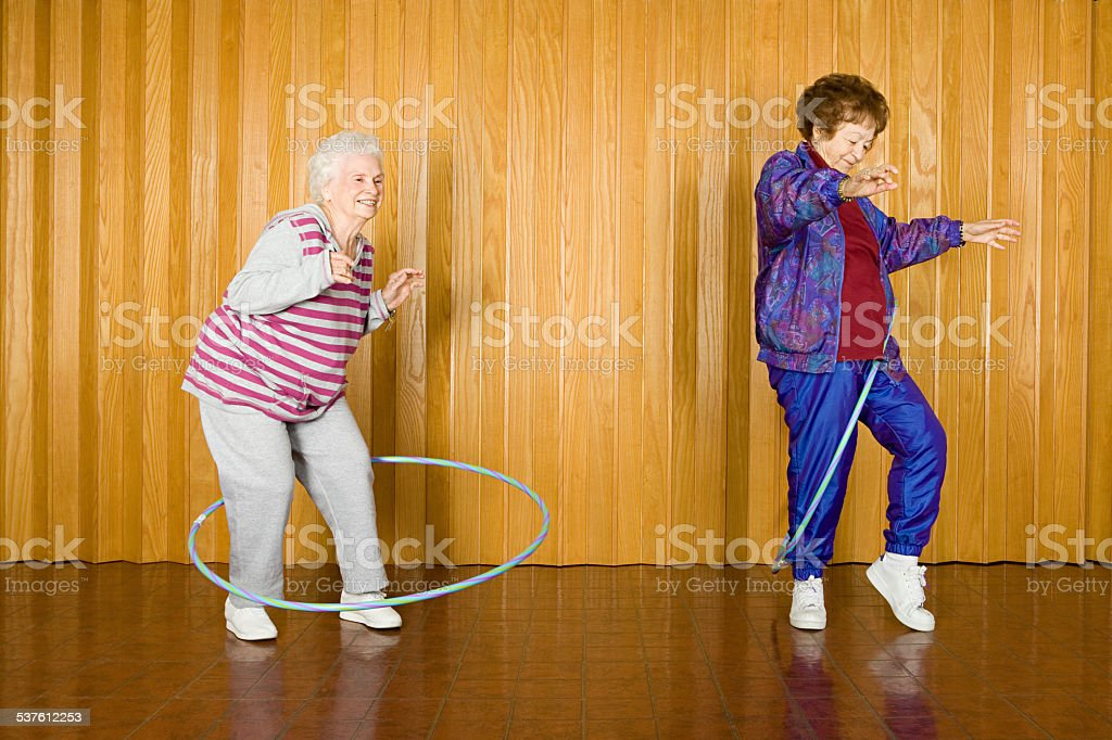 Two senior women exercising with hula hoops stock photo