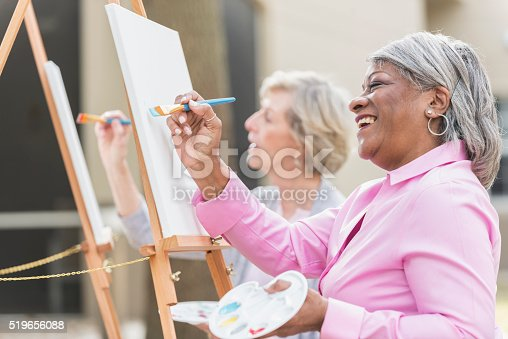 istock Two senior women having fun painting in art class 519656088