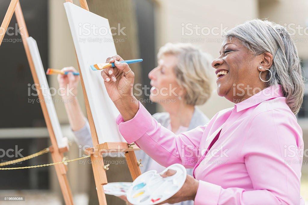 Dos mujeres mayores divirtiéndose en clase de arte de pintura - foto de stock