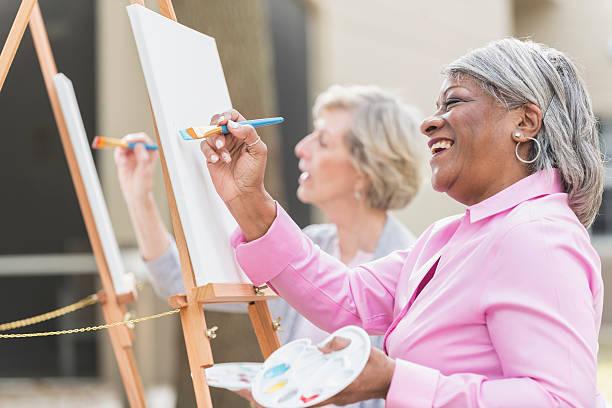 dos mujeres mayores divirtiéndose en clase de arte de pintura - clase de arte fotografías e imágenes de stock