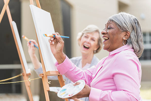 Two senior women having fun painting in art class Two multi-ethnic senior women sitting outdoors at easels painting pictures on canvases. The focus is on the African American woman who is holding a paintbrush and looking up at her artwork as she laughs. hobbies stock pictures, royalty-free photos & images