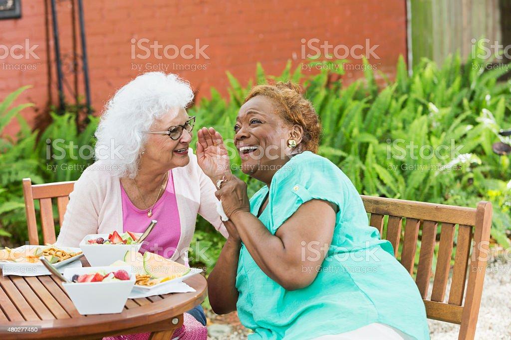 Deux femmes âgées ayant déjeuner, gossiping - Photo