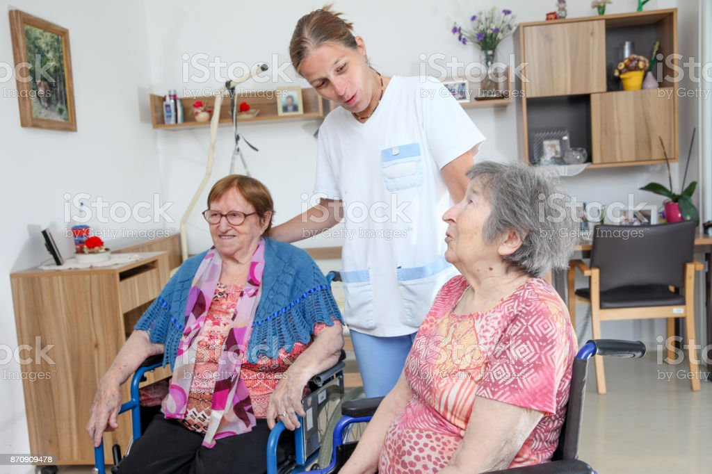 Two Senior Women on Wheelchairs and a Nurse at the Nursing Home stock photo