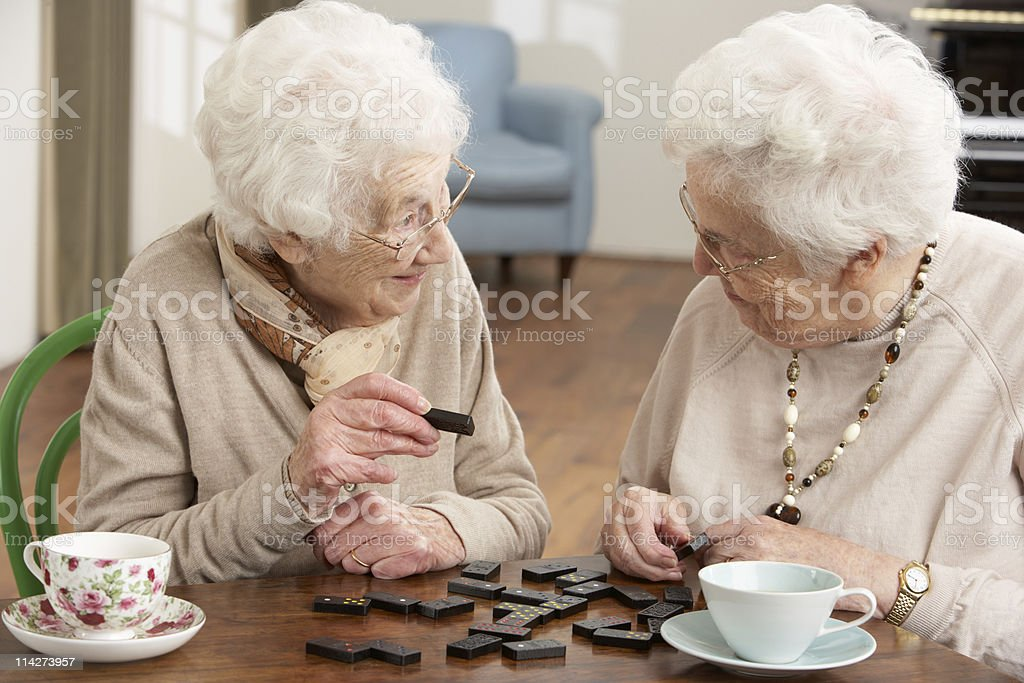 Two Senior Women Playing Dominoes At Day Care Centre stock photo