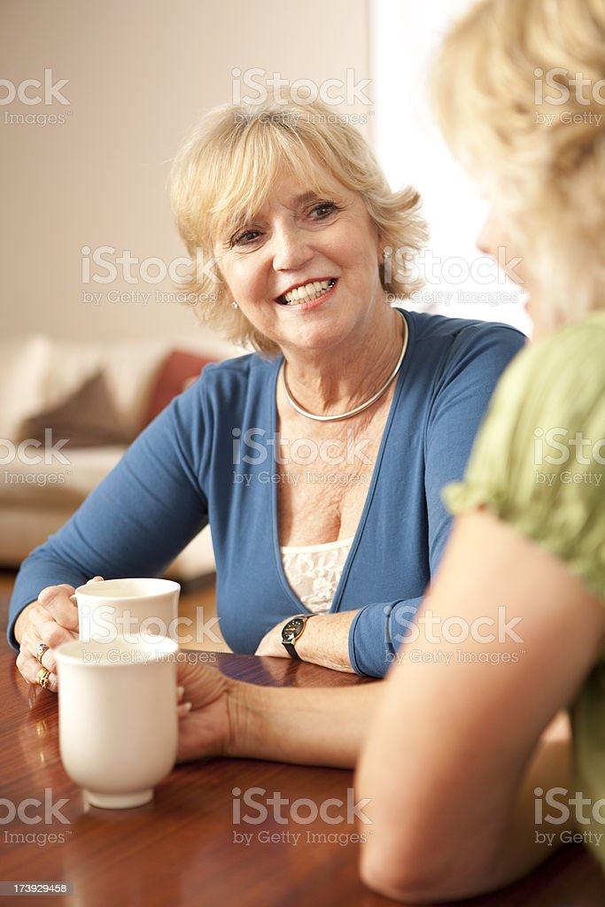 Two senior women seated, talking, with coffee cups royalty-free stock photo