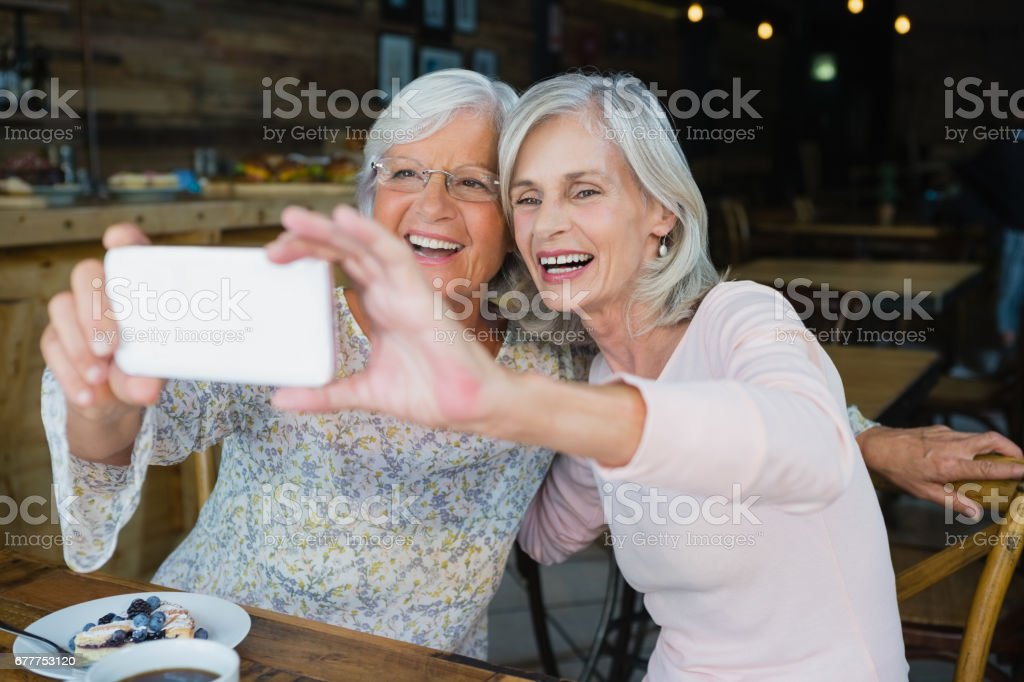 Two senior women taking selfie from mobile phone stock photo