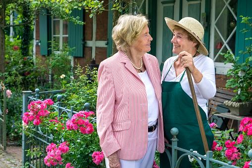 Two Senior Women Talking Together in Garden.