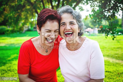 Two senior women holding each other and laughing at the outside