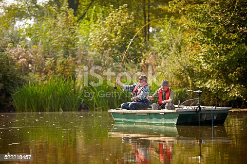 Two seniors in a boat fishing on a lake