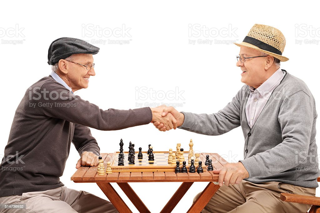 Two seniors shaking hands after a game of chess stock photo