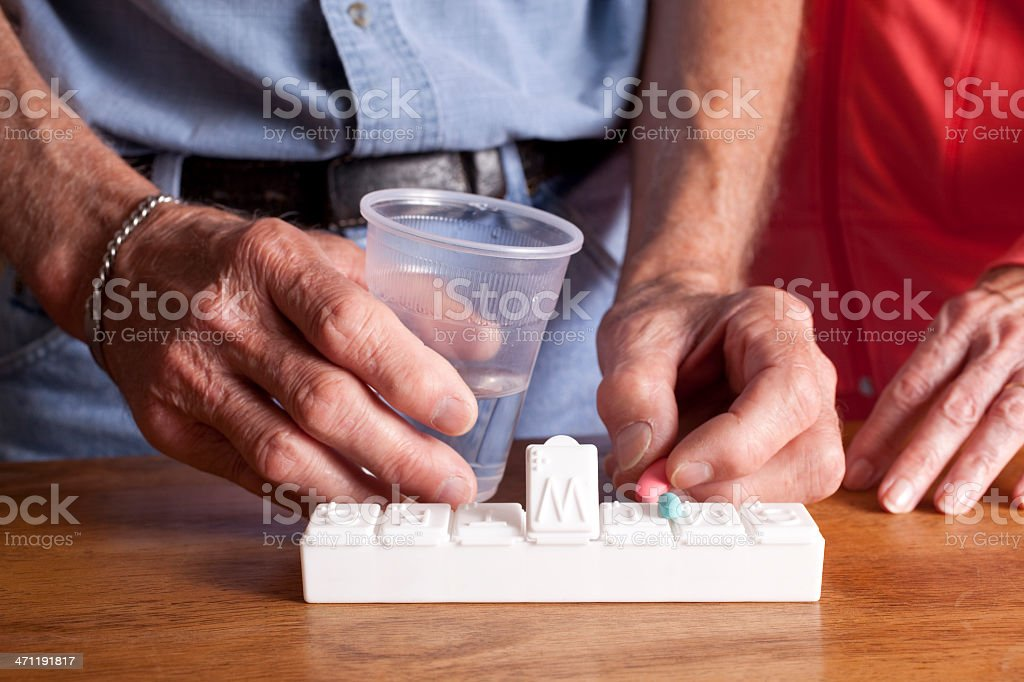 Two seniors with pill organizer and medications stock photo