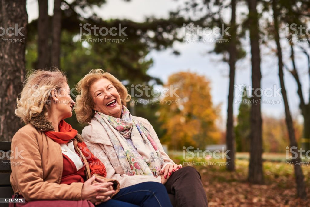 Two senoir woman laughing at the park stock photo