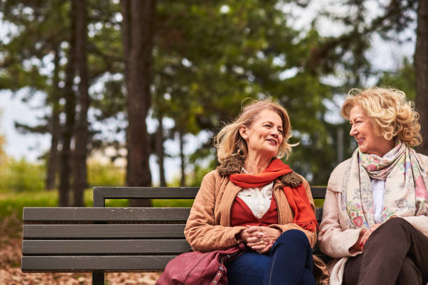 Two senoir woman talking Two senoir woman talking at the park sister stock pictures, royalty-free photos & images